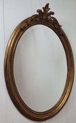 Franse spiegel met facetrand ovaal en krulkroon goud patina