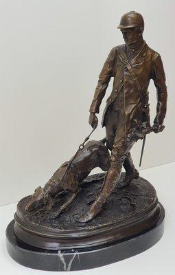 Brons beeld van jager met bloedhond in de jacht