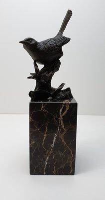 Brons beeld van vogel op tak geplaatst op marmer sokkel