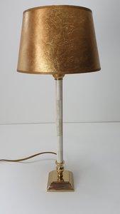 smal sfeerlampje met messing vierkant voet en roomwitte buis in combinatie met een bladgouden lampenkap